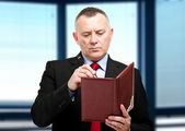 Mature businessman writing on his agenda — Stock Photo