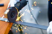 Worker using a grinder on a metal plate — Stock Photo