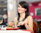 Beautiful woman eating at the restaurant — Stock Photo