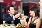 Couple toasting wineglasses in a restaurant — Stock Photo