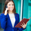 Young businesswoman at phone in an urban setting — Stock Photo