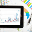 Tablet computer and financial charts — Stockfoto