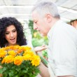Shop assistant giving a flower pot to a customer — Stock Photo