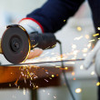 Worker grinding metal plate — Stock Photo #30861569
