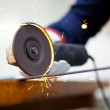 Worker grinding a metal plate — Stock Photo