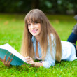 Female student lying on the grass — Stockfoto