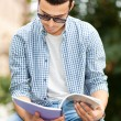 Male student reading notebook — Foto Stock