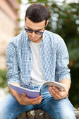 Male student reading notebook — Stock Photo