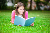 Beautiful smiling student reading book outdoor — Stock Photo
