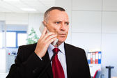 Perplexed businessman talking on the phone — Stock Photo