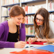 Two girls in a library — Stock Photo