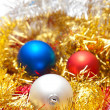 Three Christmas baubles lying on some decorations — Stock fotografie
