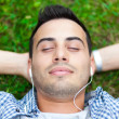 Man listening to music on the grass — Stock Photo
