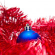 Blue Christmas ball on a red decoration — Stock Photo