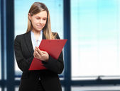 Businesswoman writing on a clipboard in an office — Stock Photo