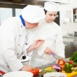 Foto Stock: Chief chef watching his assistant