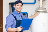 Smiling technician servicing an hot-water heater — Stock Photo