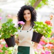 Beautiful woman holding flower pots — Stock Photo