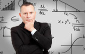 Business man with formulas on background — Stock Photo