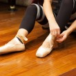 Ballerina puts on pointes — Stock Photo