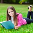 Woman reading a book in the park — Stockfoto