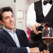 Waiter pouring wine — Stock Photo