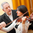 Stock Photo: Man teaching woman to play a violin