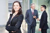 Woman posing in front of her colleagues — Stock Photo