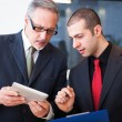Stock Photo: Businessmen using digital tablet
