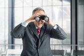 Businessman using binoculars — Stock Photo