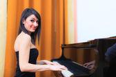 Smiling woman playing piano — Stock Photo