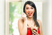 Woman eating fruit cocktail — Stock Photo