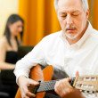 Mature mplaying classical guitar — Stock Photo #41021111