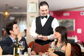 Couple ordering dinner in a restaurant — Stock Photo