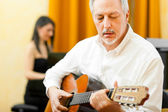 Mature man playing a classical guitar — Stock Photo