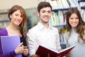 Estudiantes de pie en una biblioteca — Foto de Stock