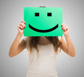 Woman holding a smiling emoticon — Stock Photo