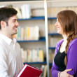 Couple talking about a book in a library — Stock Photo