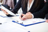 Business people taking notes — Stockfoto