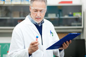 Scientist looking at a test tube — Stok fotoğraf