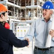 Workers shaking hands in a construction site — Stock Photo