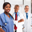 Smiling nurse in front of her medical team — Stock Photo #44647279