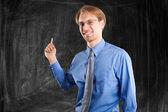 Man writing on blackboard — Stock Photo