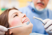 Dentist curing a female patient — Stock Photo