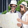 Couple of tourists holding a map — Stock Photo #48475155