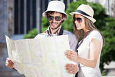 Couple of tourists holding a map — Stock Photo