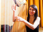 Woman playing an harp — Stockfoto