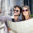 Couple of tourists holding a map — Stock Photo #48523387