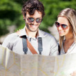 Tourists couple looking at a map — Stock Photo