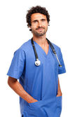 Handsome doctor with hands in pockets — Stock Photo